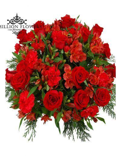 Rosas rojas, clavel rojo y alstroemelia roja, sobre caja de madera negra adornada con listón navideño. Navidad en Rojo.