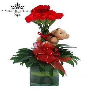 Rosa, clavel y follaje A, sobre florero de vidrio, con un oso de peluche. Hunny