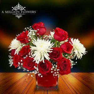 Vista frontal del Arreglo esencia de rosas en florero rojo